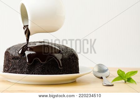 Homemade bakery, pouring chocolate sauce on top of  chocolate cake