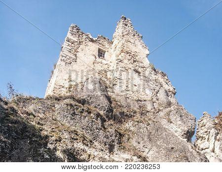 ruins of Hricovsky hrad castle in Sulovske vrchy mountains in Slovakia above Hricovske Podhradie village with clear sky