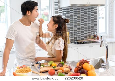 Couple together in kitchen room, Young asian woman holding vegetables to man eating each for cooking dinner healthy food menu at home couple together romantic