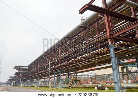 Industrial trestle for pipes. Iron pipes in the oil refinery, petrochemical plant. Pipeline.