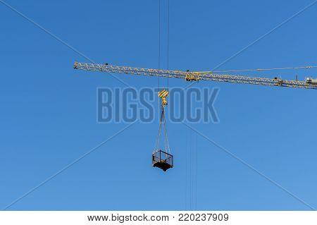 High-altitude crane lifts cargo, against the blue sky