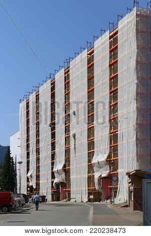 White protective canvas on scaffolding for reconstruction facade in Ruzomberok, Slovakia
