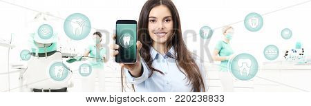 dental care smiling woman showing smart phone, teeth icons and symbols on dental clinic with dentist's chair background web banner template