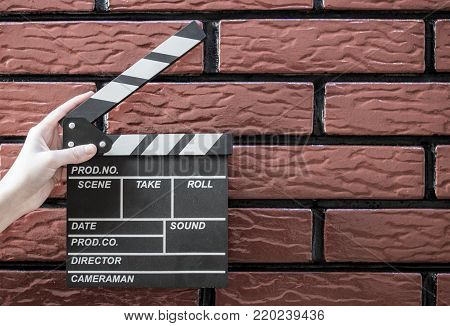 Clapper Plates, Women's Hands And A Movie Clapper With A Brick Background