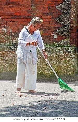 BALI, INDONESIA - DECEMBER 29, 2016: Balinese woman in traditional clothes sweeping the ground at the temple place in Bali Indonesia on 29th december 2016