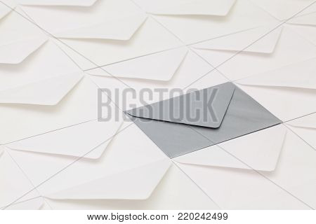 Composition with white envelopes and one silver envelope on the table.