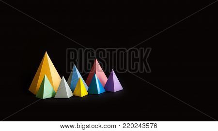 Multicolor minimalistic geometric abstract background. Bright prism pyramid triangle shape figures on black. Violet blue pink green gray yellow color solid objects. copy space
