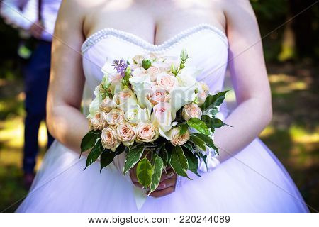 Wedding bouquet from fresh spring flowers. Bride holding white wedding bouquet close up.