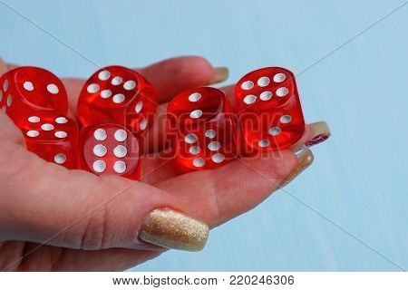 red dice in a pile on a hand on a blue background