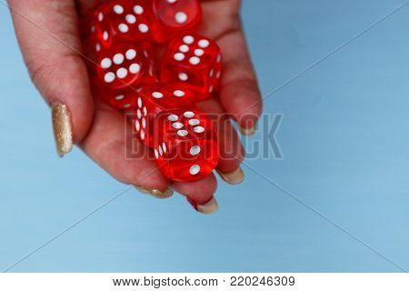 red dice in a pile on an open hand palm