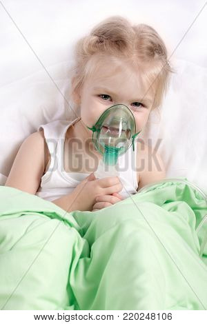 Little girl doing inhalation lying in bed. Smiling, cheerful child. Medical procedure. Treatment of the illness by inhaling medication.