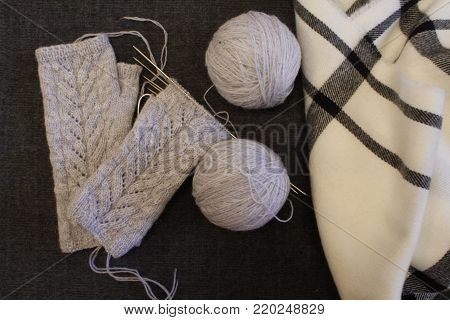 Knitting needles. Fingerless gloves knitted of gray on the background of scarves. Balls of yarn.