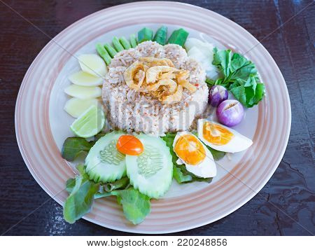 thai food cuisine named Nam Prik Long Ruea or fried rice with shrimp paste sauce, sweet chilli paste,dry shrimp, salted egg and mixed vegetable ; cucumber, yard long bean, tomato, lime, eggplant, cabbage,green oak and red oak organic hydroponic vegetables