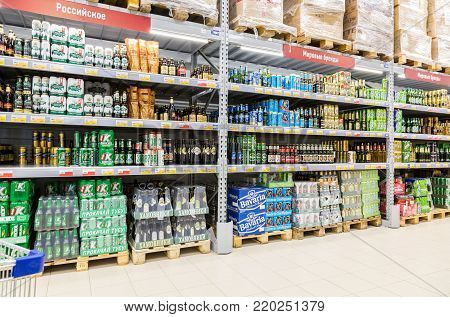 Samara, Russia - September 16, 2017: Alcoholic beverages ready for sale. Shelfs of beverage, domestic and imported beer cans and bottles at the Lenta store. One of largest food retailer in Russia