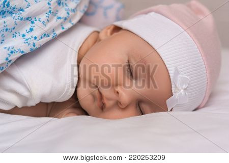 Lovely Newborn Girl Creeps On Bed, Dressed In Beautiful Pink Hat, Looks Innocently Into Camera. Smal