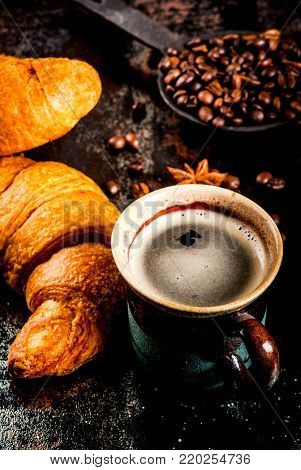Homemade continental breakfast, coffee with spice, cane sugar, croissants. jam on a black rusty metal table, copy space