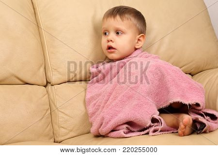 small child wrapped in a towel after bathing