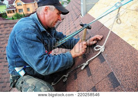 KYIV, UKRAINE - January, 14, 2018: Roofer laying asphalt shingles. Roofer with safety kit on the house roof installing, repair asphalt shingles.Roofing construction. Roofer's Kits for Fall Protection.