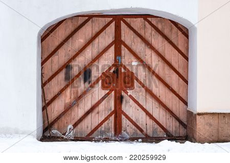Old big door. Entrance with an arched double door, made from hard wood with metal frame