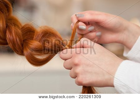 Hairdresser makes hairstyle girl with long red hair in a beauty salon. Create curls with curling irons. Professional hair care.