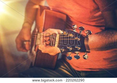 Mastering Acoustic Guitar. Caucasian Musician Playing on Guitar.