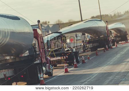 Wind Turbine Blades Shipping. Trucks Convoy with Elements of Wind Turbines.