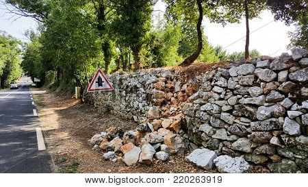 The damaged old wall next to the road with stones.
