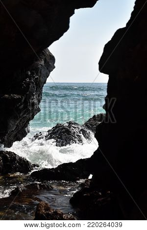 Seascape through a rocky niche with spray and blue water