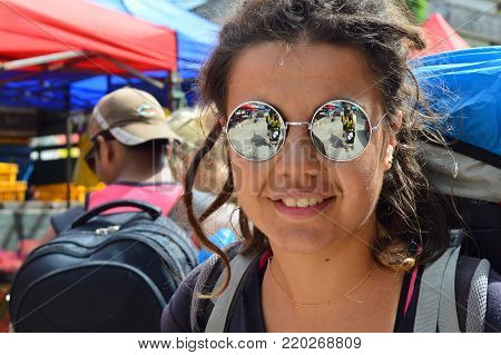 Girl with dreadlocks in glasses traveler during the summer holidays will travel to Asia. Backpacker have a backpack behind shoulders. Nice, tanned tourist.