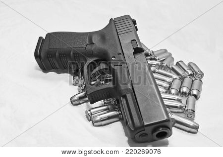 A semi-automatic pistol laying on a pile of bullets with a white background, shot in black and white