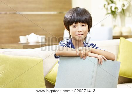 8-year-old little asian boy sitting on sofa holding a book looking at camera smiling.