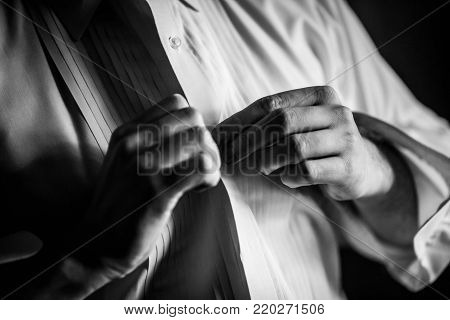 Black and white photo of a man buttoning his dress shirt.
