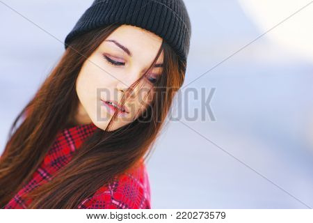 Portrait of young sad girl with beautiful hair, lowered look at the blurred background sky, close-up.