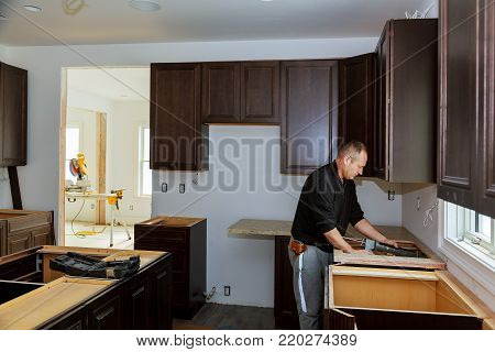 Carpenter installing cabinets and counter top in a kitchen. Kitchen more functional with a sink, cooktop, and partially installed