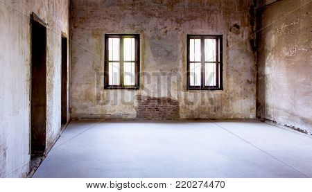 Overview of the empty room with old windows and doors. Abandoned empty room with the light shining through the window.