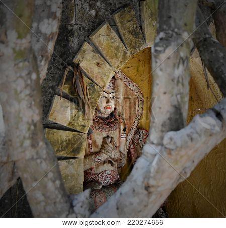 Hidden balinese spiritual wooden statue in a niche