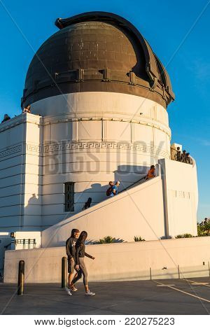 LOS ANGELES, CALIFORNIA - NOVEMBER 19, 2017:  People walk by the dome housing a Zeiss refracting telescope at Griffith Observatory, a popular destination with free nightly public telescope viewing.
