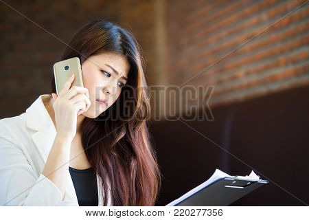 Asian Working Women Age Between 25-35 Years Old Speking With Cell Phone And Looking At A Paper.