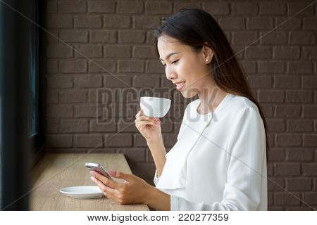 Portrait Of Asian Business Women Age Between 25-30 Years Old In White Suit Drinking A Coffee In The