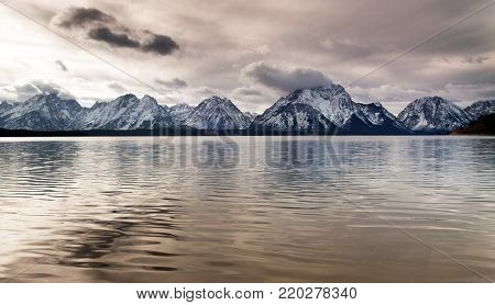 Tall ridges of the Rocky Mountain Range reflect in the  lake called Jackson in Wyoming