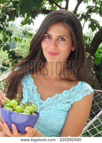 Latin woman eat grape fruit on garden hammock