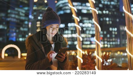 Woman use of smart phone in the city at night, surf online on smart phone with urban city background, woman wearing winter jacket