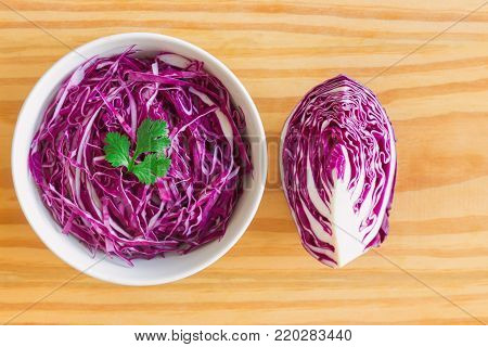 Sliced fresh purple cabbage in white bowl to shredded and decorate with coriander. Sliced cabbage in top view flat lay on wood table. Prepare vegetable for cooking cabbage salad or coleslaw. Homemade food concept of fresh purple cabbage..