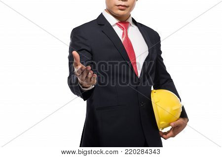 Businessman wearing a helmet standing and reaching hand for handshake, isolated on white