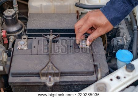 Hand checking and repairing car battery for travel safety concept