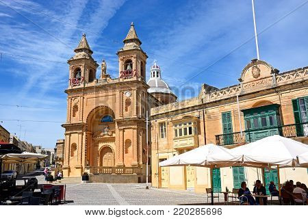 MARSAXLOKK, MALTA - APRIL 1, 2017 - People relaxing at pavement cafes with the parish church of Our Lady of Pompei to the rear, Marsaxlokk, Malta, Europe, April 1, 2017.