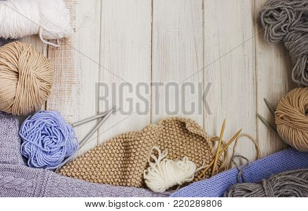 Knitting, needles and yarn on white wooden background. Copy space