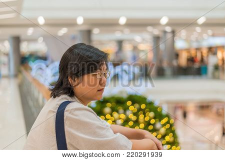 Asian woman 40s white skin plump body with backpack waiting in department store or shopping mall with pine tree in merry christmas and new year celebration poster