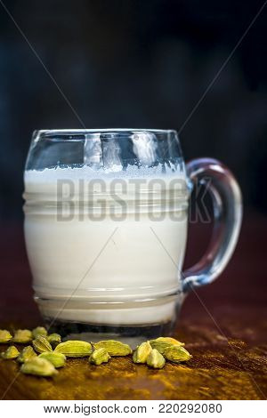 Sweetened Milk With Some Green Cardamoms On Brown Wooden Surface.