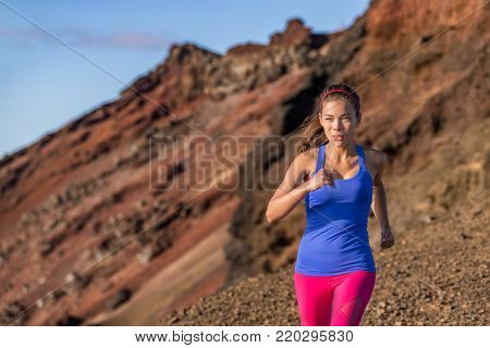 Trail runner Asian woman athlete running in desert mountain landscape. Determination and motivation on endurance race training in outdoors nature.